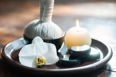Spa background. Towel, candles, flowers, massaging stones and herbal balls. Massage, oriental therapy, wellbeing and meditation.