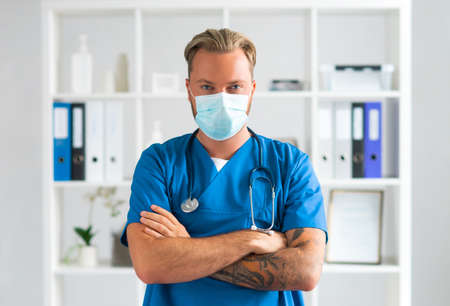 Professional medical doctor in hospital office, Portrait of young and confident physician in protective mask. Archivio Fotografico