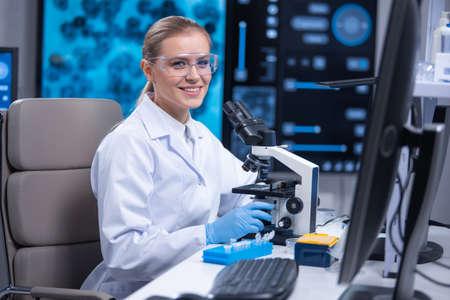 Professional female scientist is working on a vaccine in a scientific research laboratory. Genetic engineer workplace. Technology and science concept. Archivio Fotografico