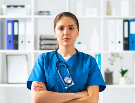 Professional medical doctor working in hospital office, Portrait of young and attractive female physician in protective mask.