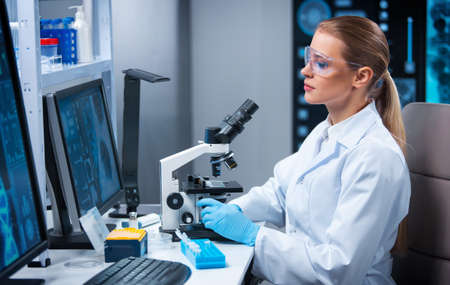 Female doctor works in a modern scientific laboratory using equipment and computer technologies. The scientist does research and develops new vaccines. Science and healthcare concept.