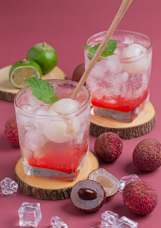 Lychee juicy punch drink with mint in glass on wooden board and pink background.