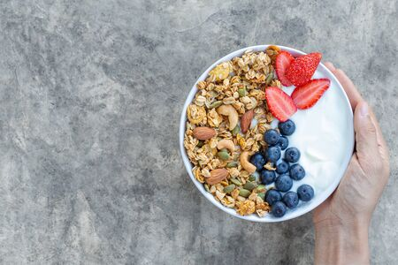 Holding bowl of homemade granola with yogurt and fresh berries on bright gray concrete background from top view.