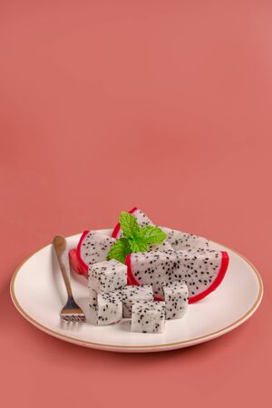 Slice of fresh ripe Dragon fruit with mint on white plate for dessert on pink background