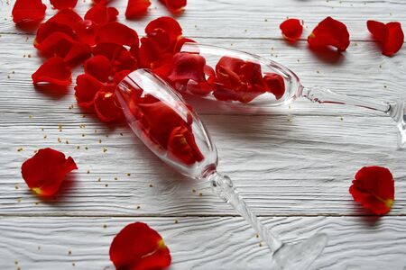 Red rose petals spilled out of wine glasses. Side view. Valentines Day background. Фото со стока