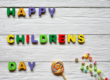 Multi-colored wooden letters making up the words Happy childrens day and multi-colored sucking sweets on a white wooden background. Top view. Bright festive background.