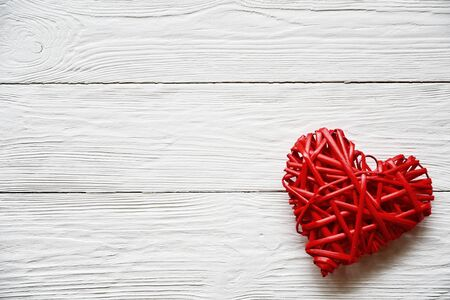 Big red rattan heart on a white wooden background. Close-up. Top view. Valentines Day background.