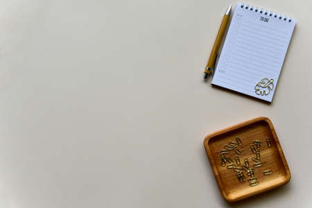 Notepad with wooden pen and wooden tray with golden staples on a beige paper background. Top view. Copy space. Flat lay.