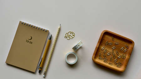 Notepad with pen and pencil, wooden tray with golden staples and adhesive tape on a beige paper background. Close-up. Top view. Foto de archivo