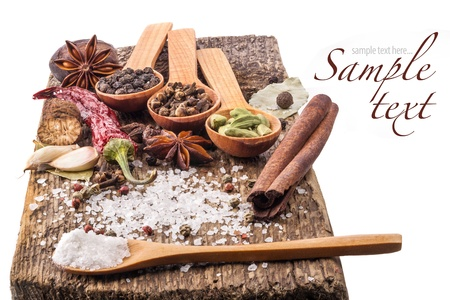 Spices on wooden table with spoons isolated on white background Stock Photo
