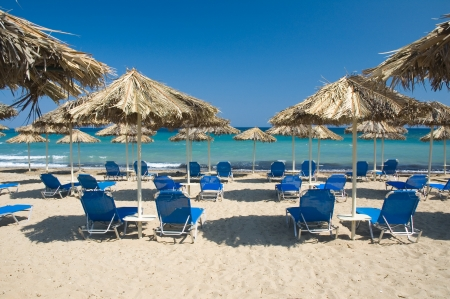 tourist resort: Loungers under palm tree leaves umbrellas on the beach Stock Photo