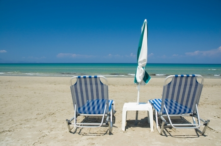 Two loungers and an umbrella on the beach photo