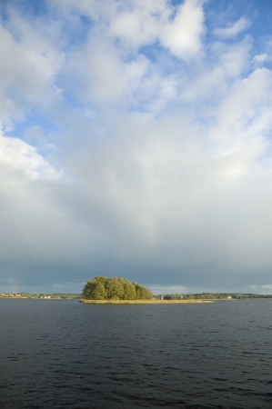 masuria: Small island at sunset against stormy dark clouds, Masuria district, Poland