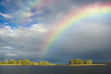 Rainbow over a small sunlit island, Masuria district, Poland