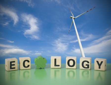 Word ECOLOGY made of letters on wooden blocks with a windmill in the background  Concept of ecological, healthy world  photo