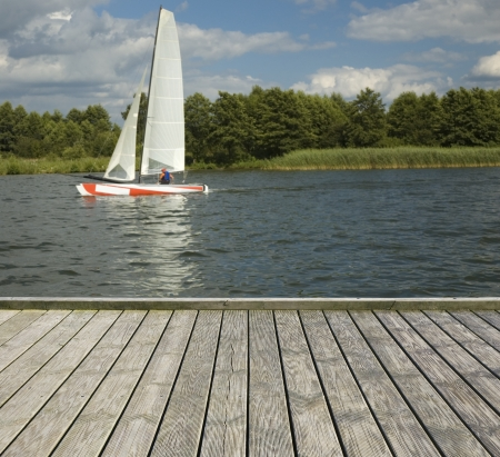 Empty wooden jetty on the lake shore with a catamaran in the background photo