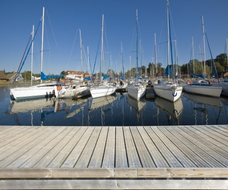 Empty wooden jetty on the lake shore with yachts moored in marina photo