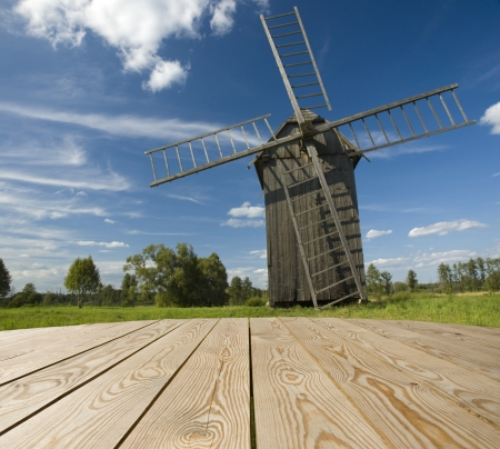 Empty wooden tabletop  with wooden windmill - base for flour product photo