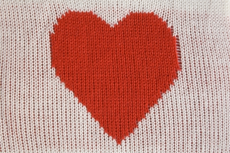 Knitted red heart shape on white  photo