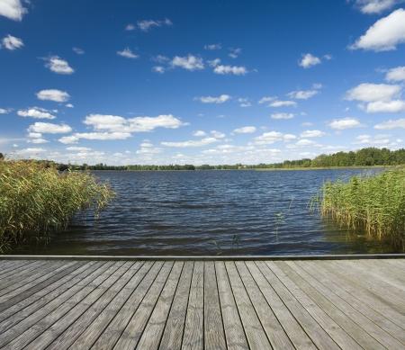 湖のほとりの空の木製桟橋