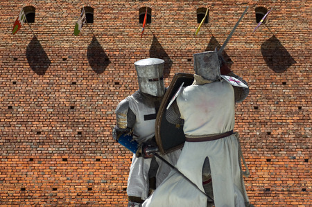 Armored fighting knights with medieval castle in the background, Leczyca, Poland photo