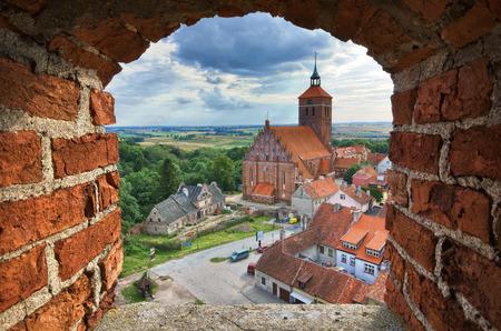 View of old church through the castle tower window, Reszel, Warmia, Poland Stock Photo