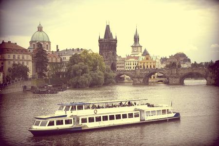 vltava: Vintage view of ship on Vltava river with Charles Bridge in the background, Prague