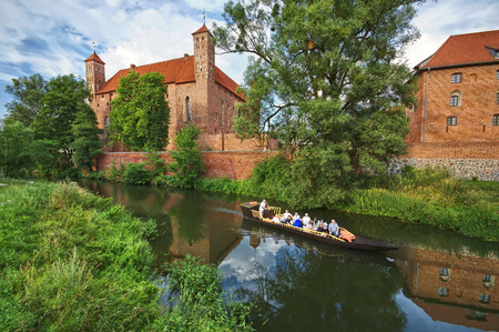 warmia: Pleasure boat on moat by medieval Gothic castle in Lidzbark Warminski, Poland Editorial