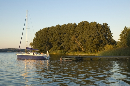 mazury: Sailboat moored by wooden jetty on a lakeshore at the break of dawn, Mazury, Poland Stock Photo