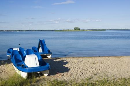 lakeshore: Pedal boats moored on lakeshore, Niegocin Lake, Mazury, Poland