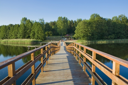 lakeshore: Footbridge on Wydminskie Lake, beautiful lakeshore with swimming pool and park in the background, Wydminy, Poland
