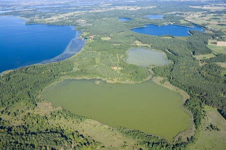 farther: Aerial view of beautiful autumnal landscape of Mazury, Poland - very shallow Skarz Lake in the foreground, farther on the left Dargin Lake, on the right Dgal and Warniak Lakes, Swiecajty Lake in the background