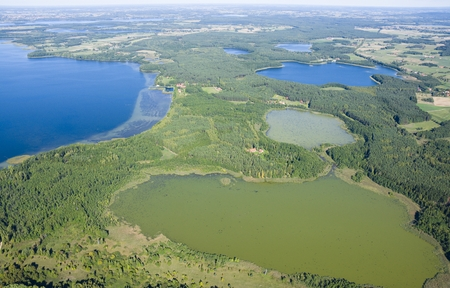 farther: Aerial view of beautiful autumnal landscape of Mazury, Poland - very shallow Skarz Lake in the foreground, farther on the left Dargin Lake, on the right Dgal and Warniak Lakes