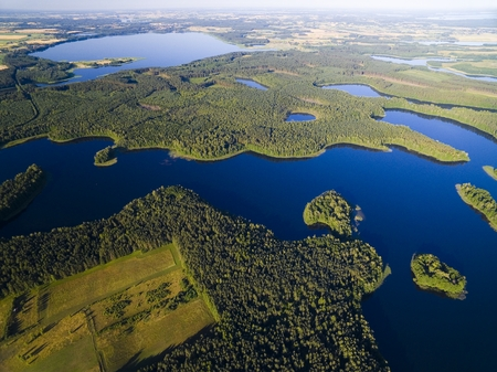 Aerial view of small uninhabited island (Wyspa Pozeracza Serc) on lake with sky reflected in calm water, Krzywa Kuta Lake, Mazury, Poland 版權商用圖片