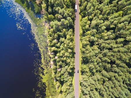 Aerial view of straight road through the mixed forest by the lakeshore, Mazury, Poland Stockfoto