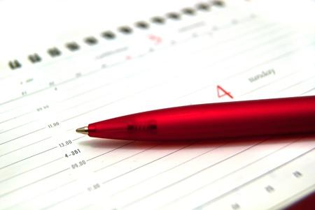 Red pen on diary. On white photo