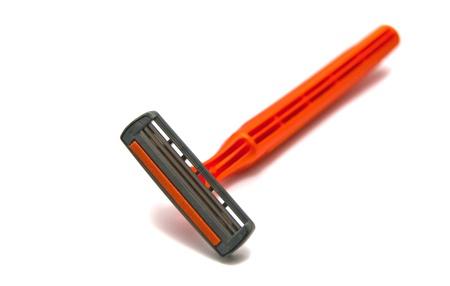 utiles de aseo personal: cuchillas de afeitar de color naranja sobre fondo blanco