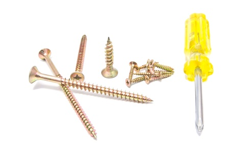 Golden screws and yellow screwdriver on white background photo