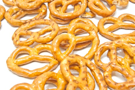many tasty salted pretzels closeup on white
