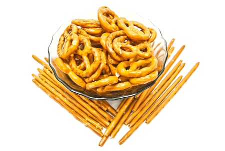 many tasty salted pretzels and breadsticks on white closeup