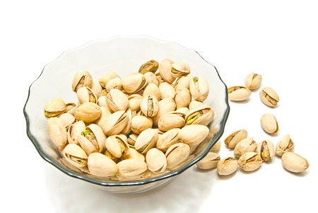 glass plate with tasty pistachios on white background Stock Photo