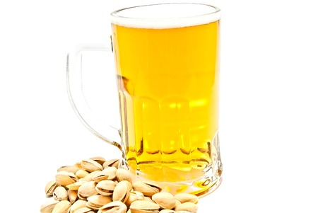 pistachios and mug of beer closeup on white background