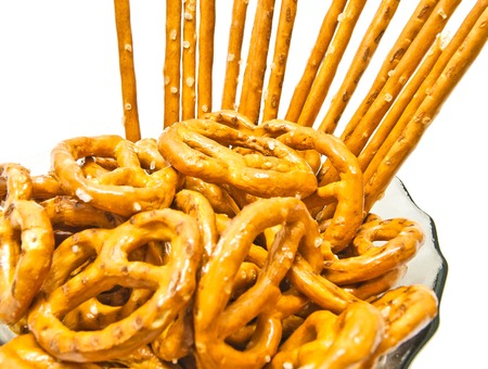 tasty salted pretzels and breadsticks closeup on white