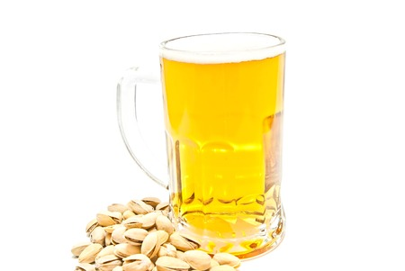 pistachios and mug of beer on white background