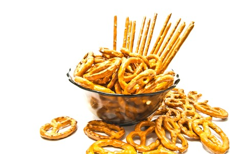 salted pretzels and breadsticks on a plate on white