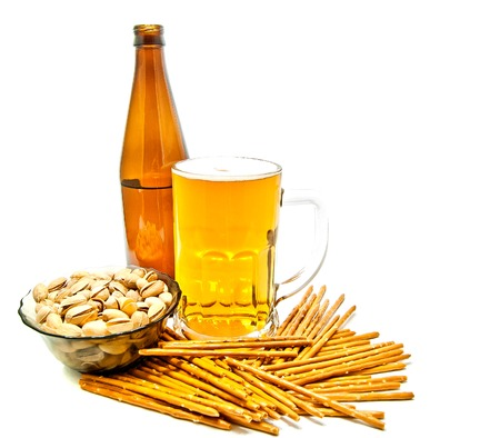 breadsticks, pistachios and light beer on white background