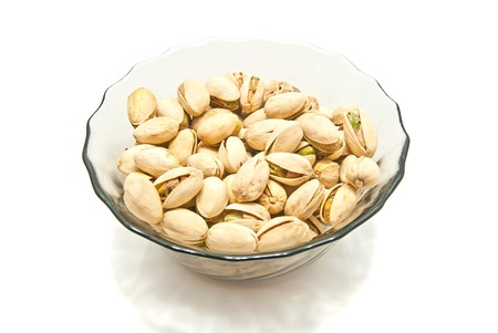 pistachios: dish with roasted pistachios closeup on white Stock Photo