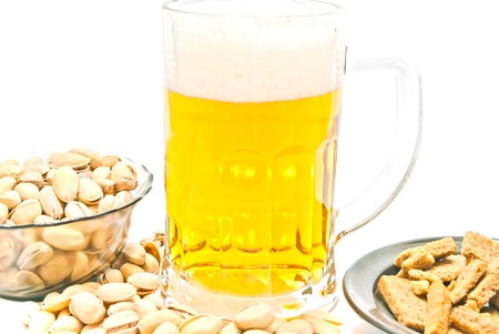 crisps, pistachios and glass of beer closeup on white