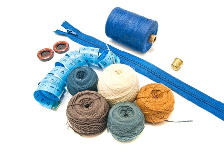 different balls of yarn and blue meter on white background