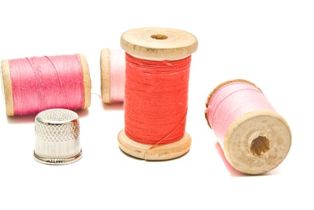 thimble and spools of thread closeup on white